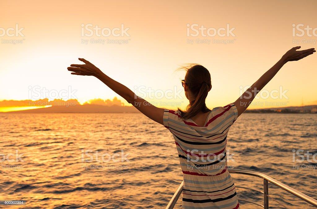 Woman enjoying beautiful sunset stock photo