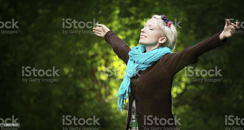 Woman enjoying being outdoor with arms outstretched royalty-free stock photo