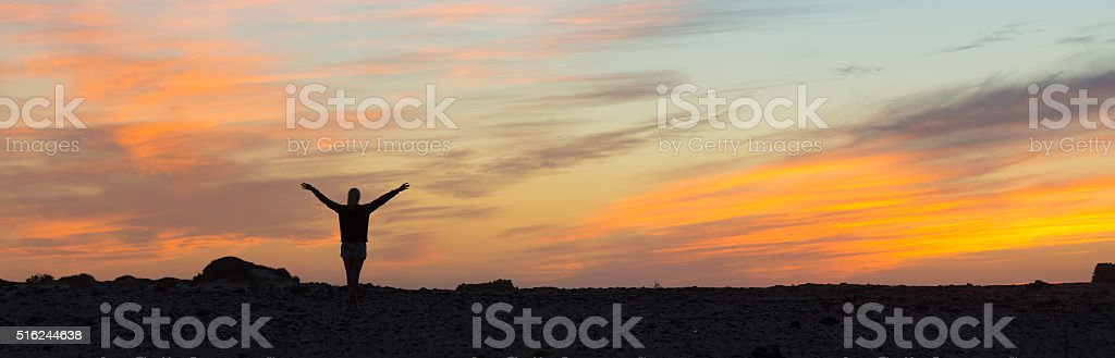 Woman enjoying freedom at sunset. stock photo