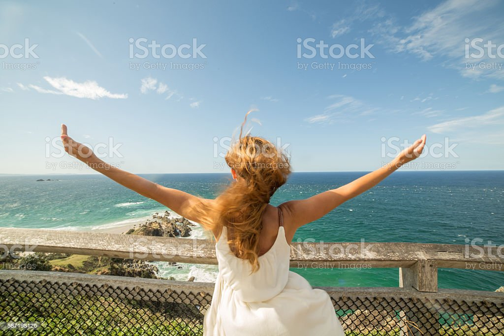Woman enjoying freedom in nature, arms outstretched to the sea stock photo