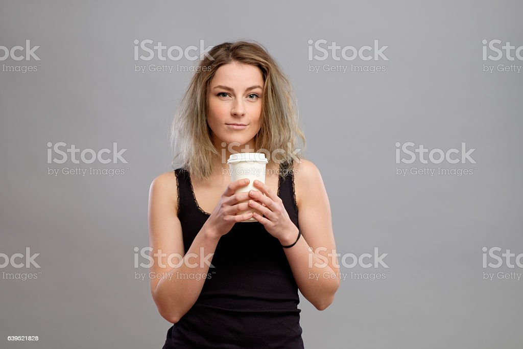 Woman enjoying hot drink in disposable paper cup stock photo