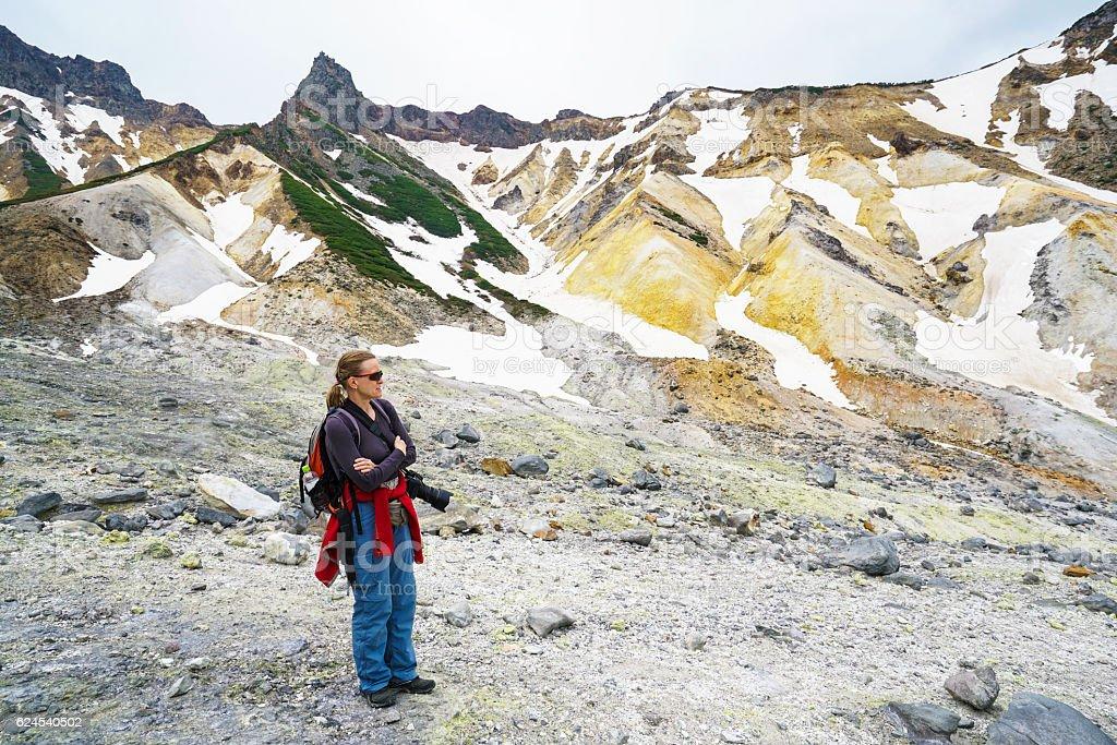 Woman enjoying in crater of Tokachidake active volcano, Hokkaido Japan stock photo