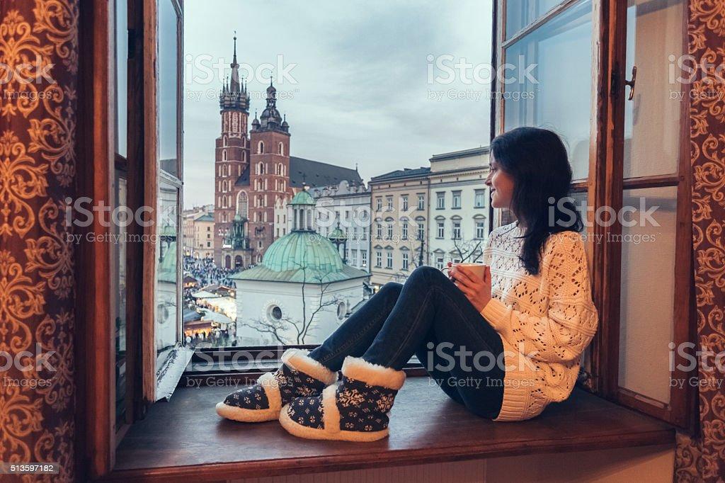 Woman enjoying Krakow city from the window stock photo