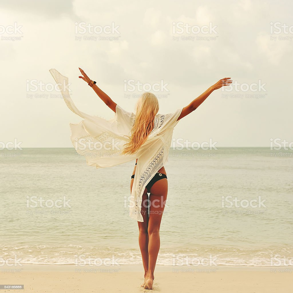 Woman enjoying nature at the beach. Arms wide open, freedom stock photo