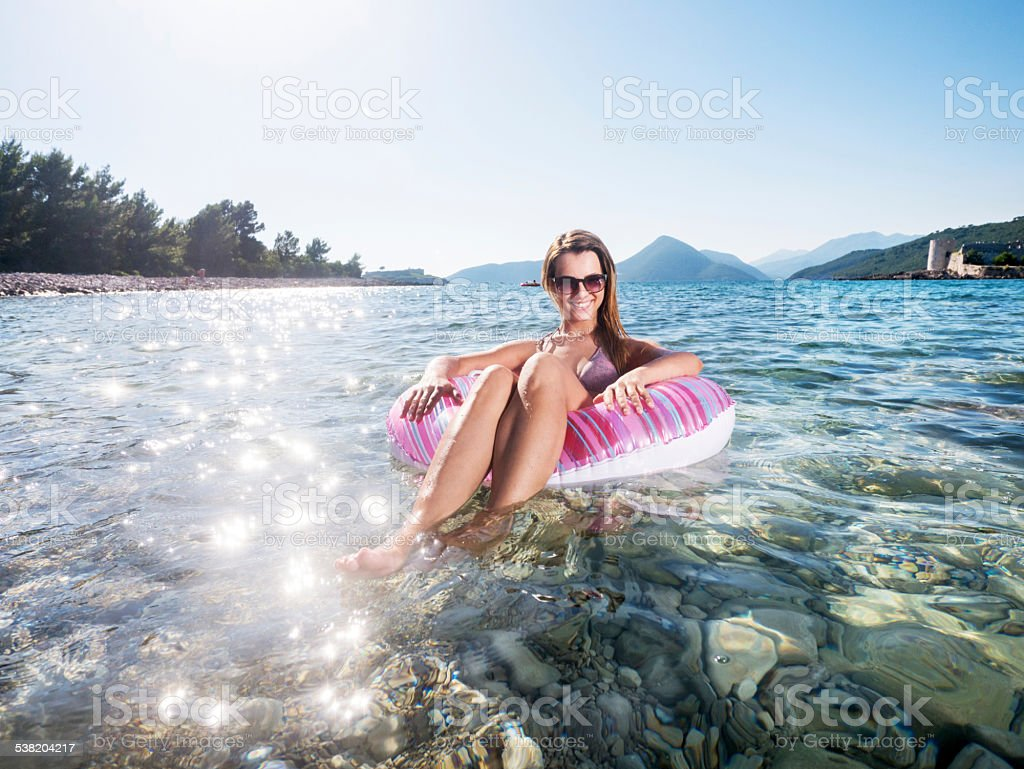 Woman enjoying on inflatable tube. stock photo