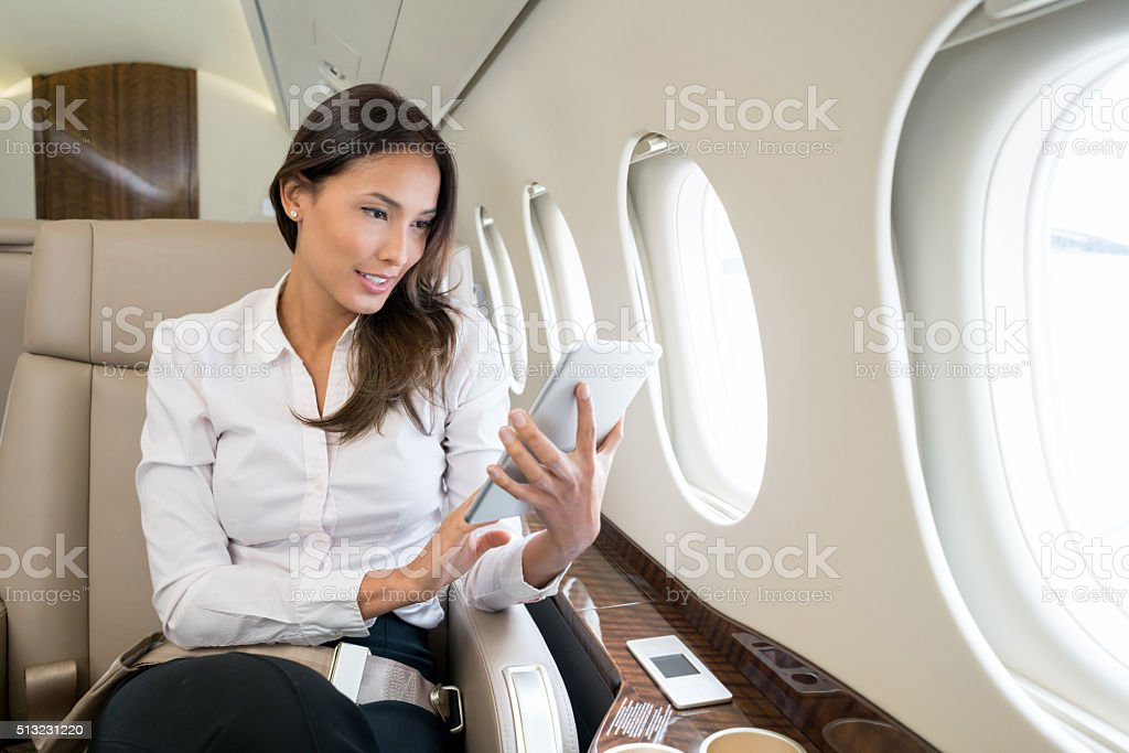 Woman enjoying onboard entertainment in her tablet computer stock photo