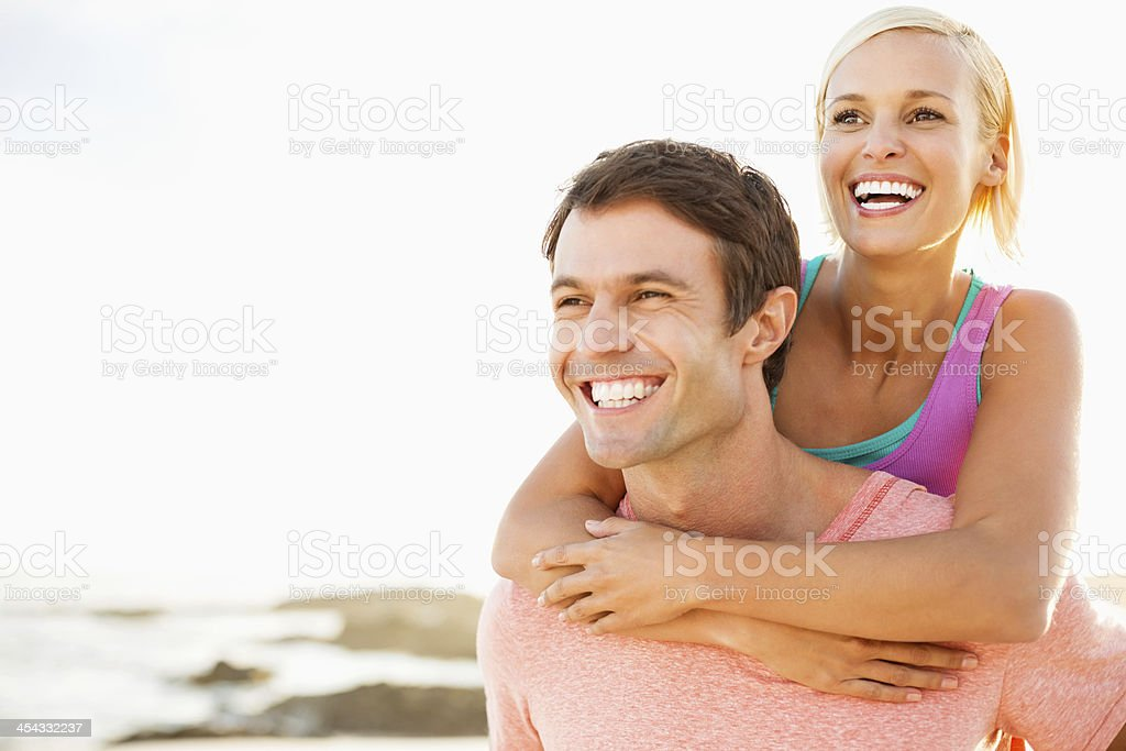 Woman Enjoying Piggyback Ride With Man Against Clear Sky stock photo
