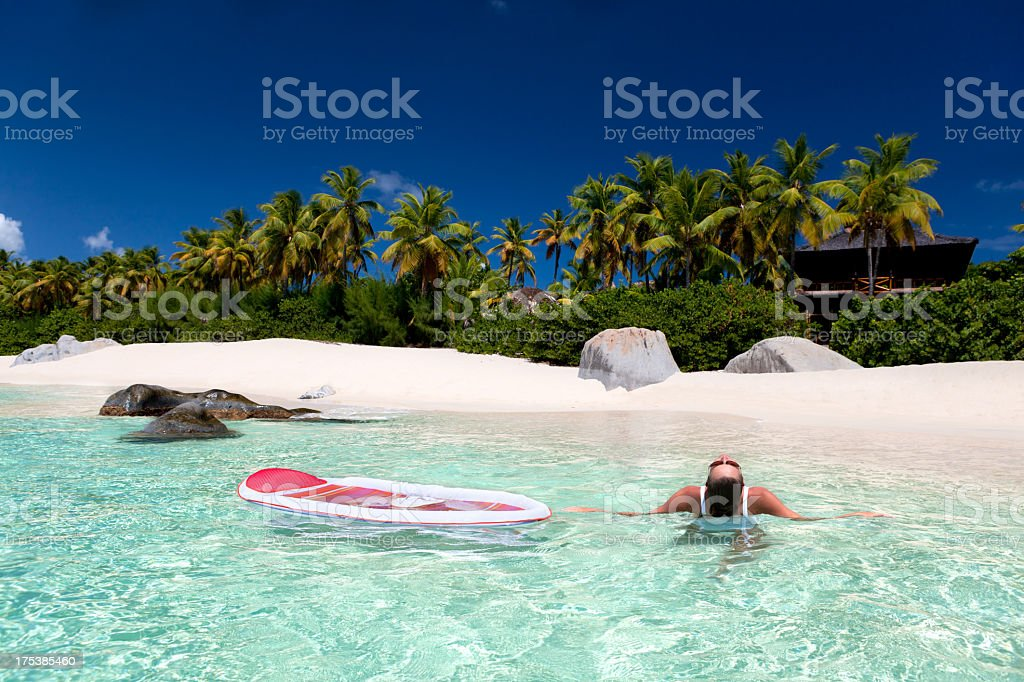 woman enjoying refreshing water at a tropical Caribbean beach stock photo