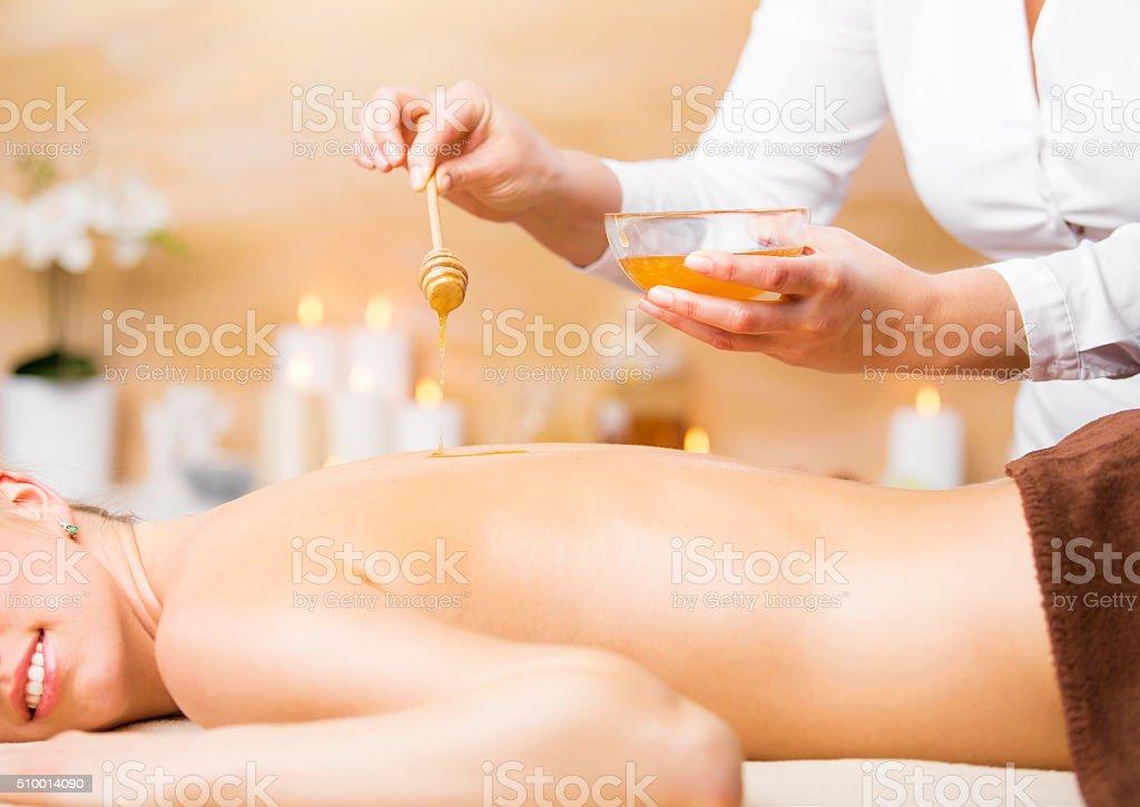 Woman enjoying spa treatment with honey stock photo