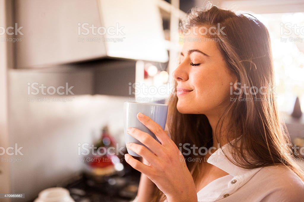 Woman enjoying the aroma of her cup of coffee stock photo