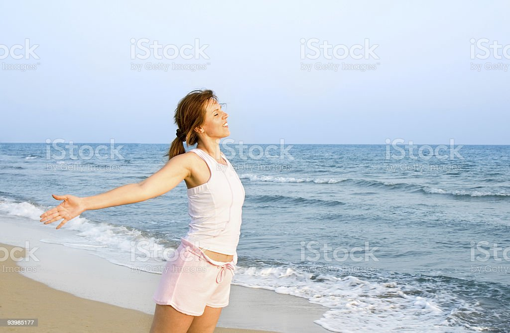 A woman enjoying the sea breeze during sunset royalty-free stock photo