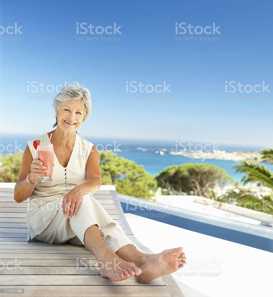 Woman enjoying vacation with a glass of milkshake royalty-free stock photo