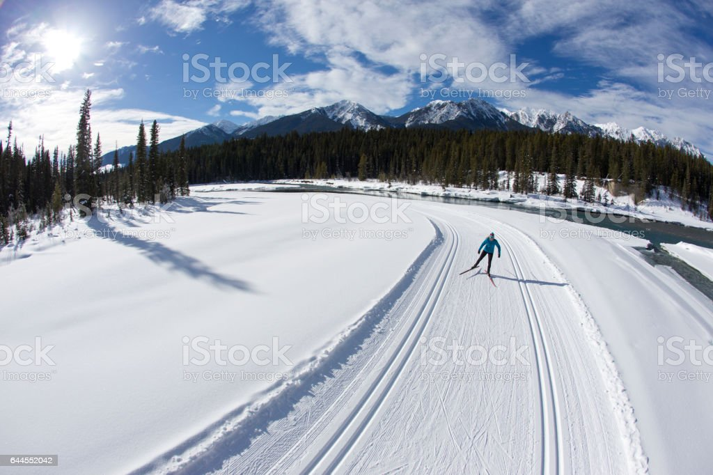 A woman enjoys a cross-country skate ski next to a river in British Columbia, Canada. stock photo