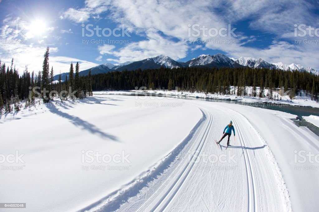 A woman enjoys a cross-country skate ski next to a river in the Rocky Mountains of Canada. stock photo