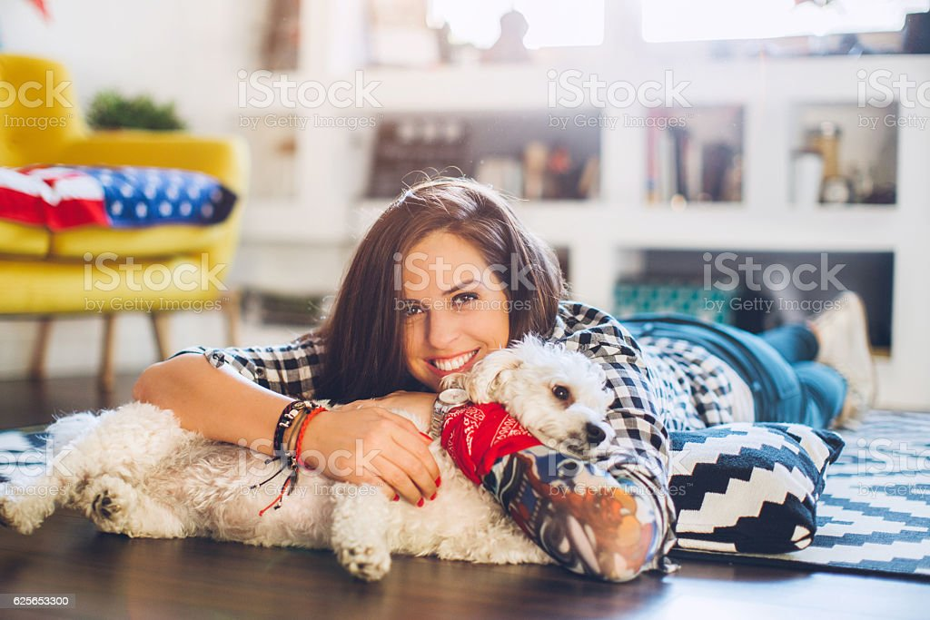 Woman enjoys with small dog on floor stock photo
