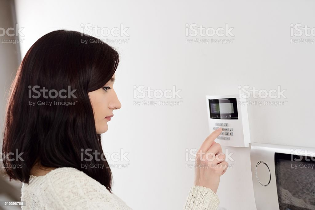 woman entering code on keypad of home security alarm stock photo
