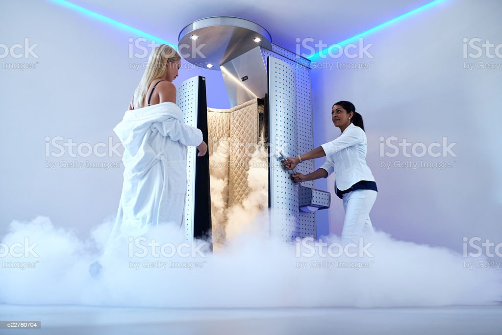 Woman entering freezing booth at the cosmetology clinic stock photo