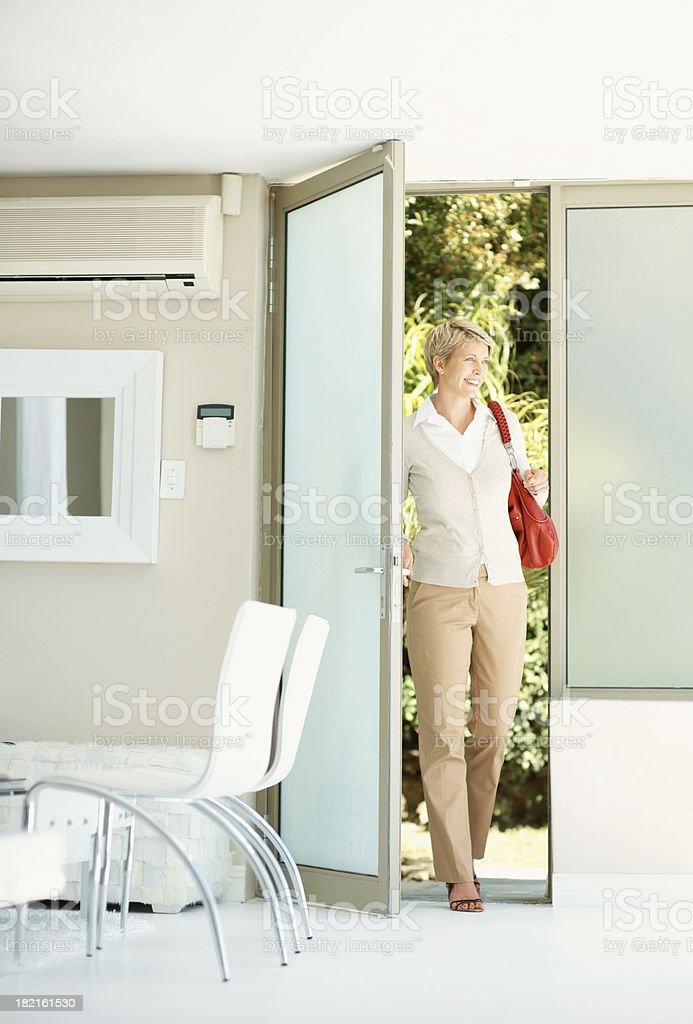 Woman entering her house through the door stock photo