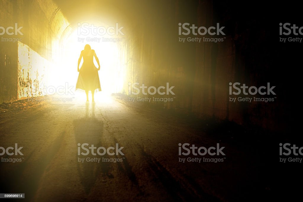 Woman Entering Light At End Of Tunnel stock photo