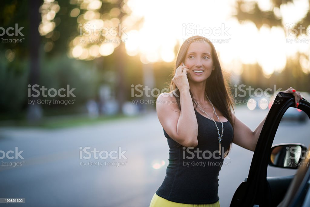 Woman entering the car with mobile phone stock photo