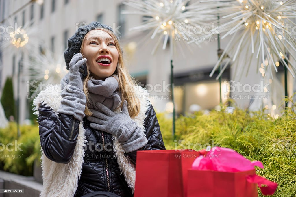Woman enthusiastically conversing on phone on cold day stock photo