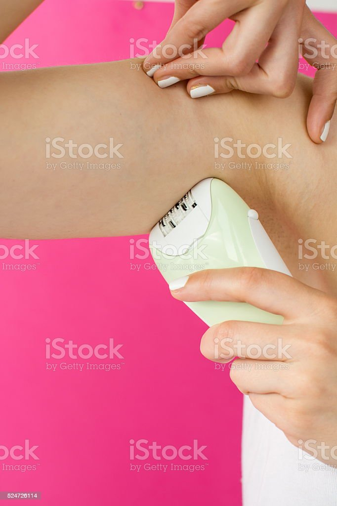 Woman epilates her armpit with an epilator stock photo