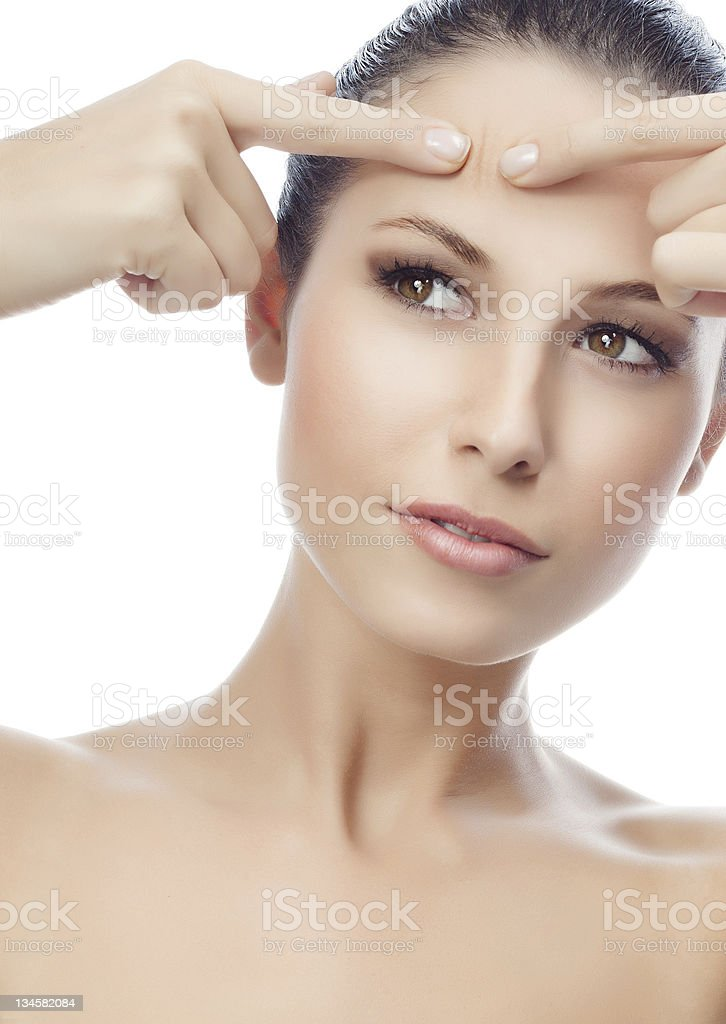A woman examining a skin blemish on her face stock photo