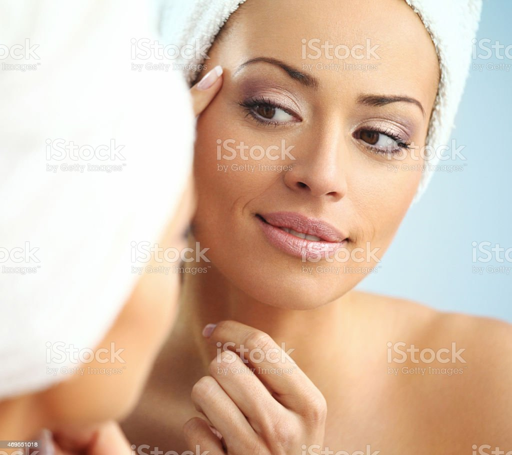 Woman examining her sking in bathroom. stock photo