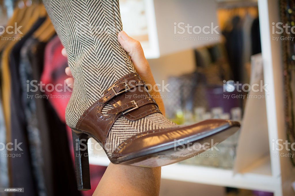 Woman examins a Vintage high heel boot stock photo