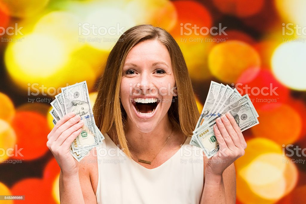 Woman excited by money stock photo