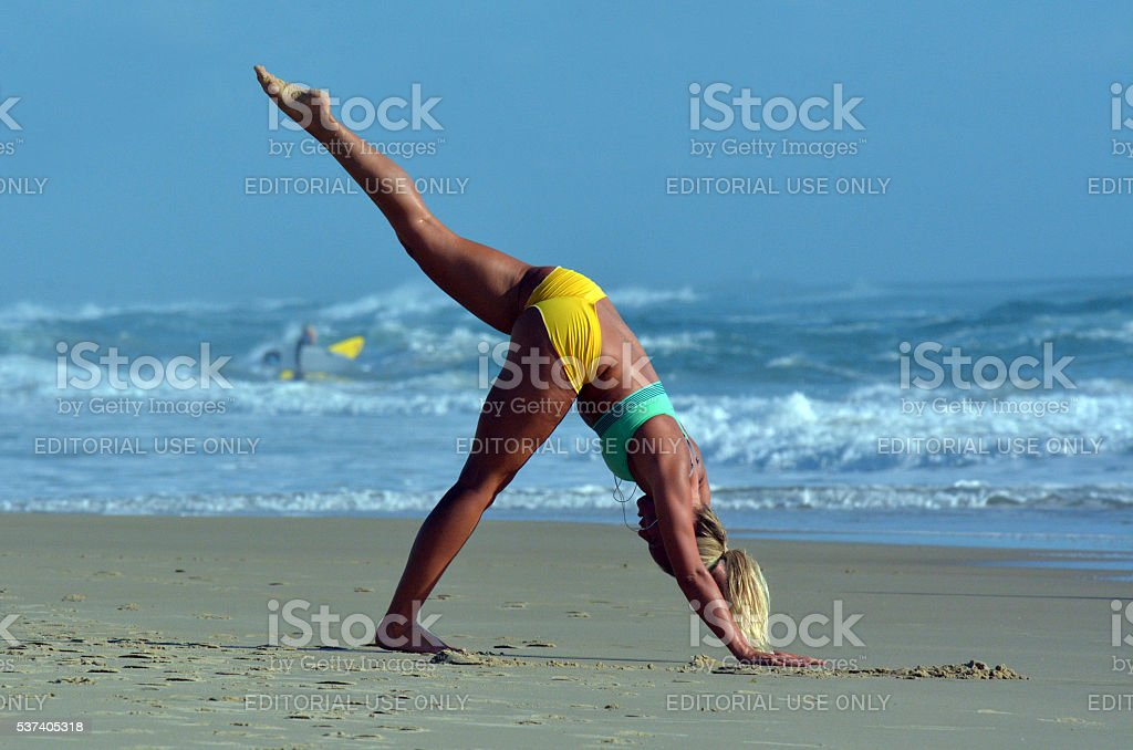 Woman exercise Yoga on the beach stock photo