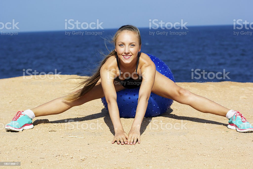 Woman exercises with a fit ball on the beach royalty-free stock photo