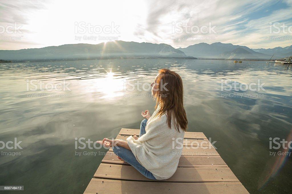 Woman exercises yoga on lake pier stock photo