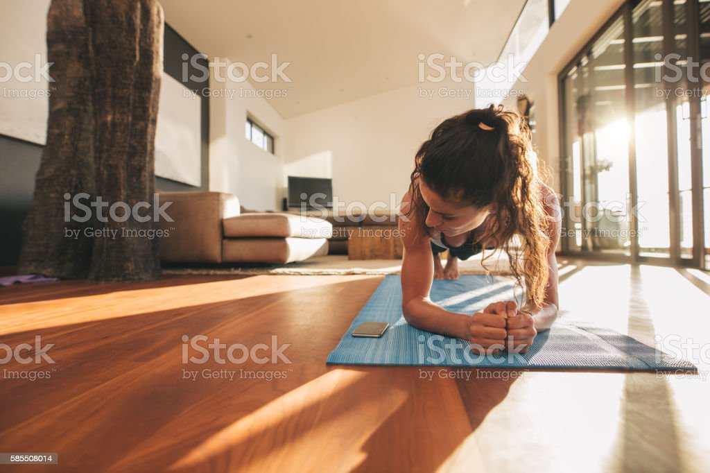 Woman exercising and looking at her mobile phone stock photo