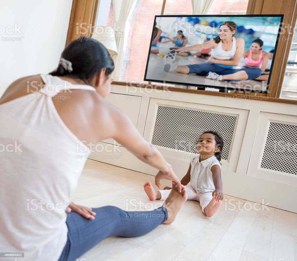 Woman exercising at home and watching the baby stock photo