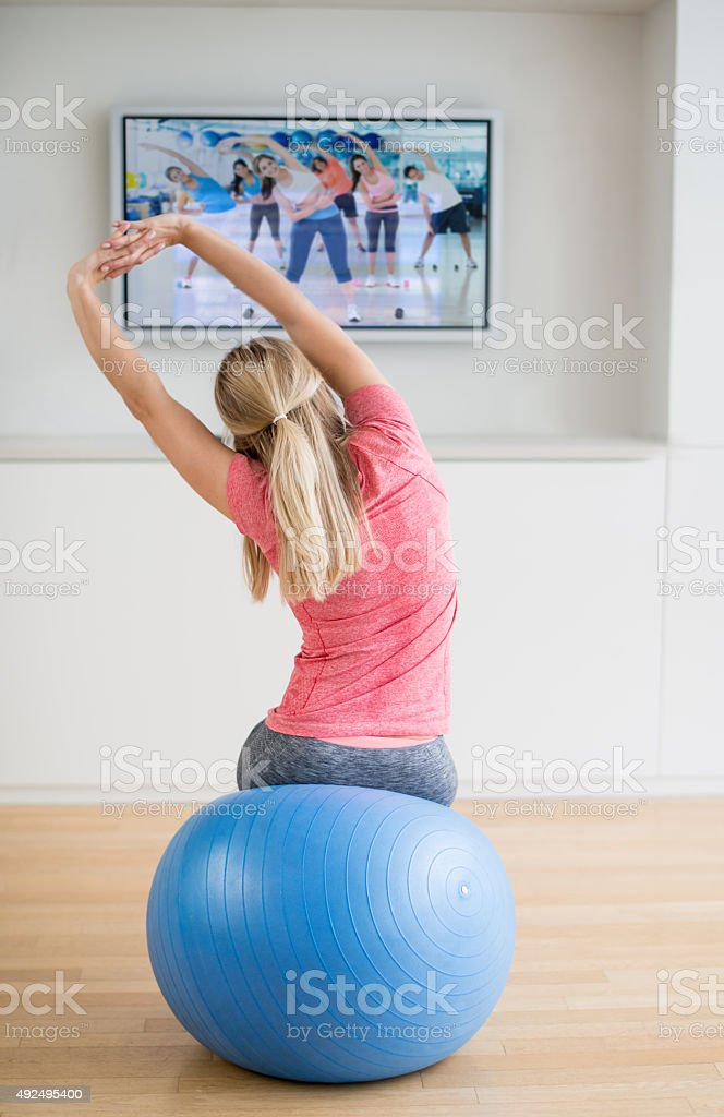 Woman exercising at home watching a DVD stock photo