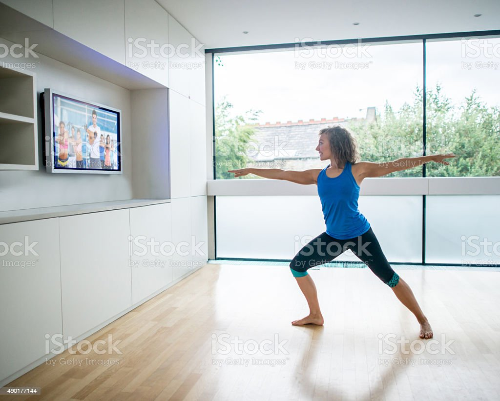 Woman exercising at home watching a Pilates DVD stock photo