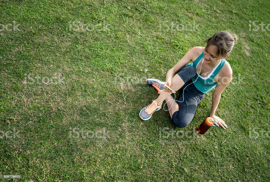 Woman exercising at the park and listening to music stock photo