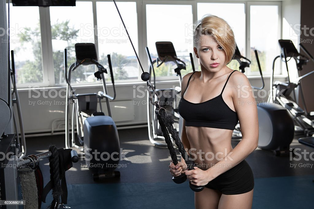 Woman Exercising Back On Machine In The Gym stock photo