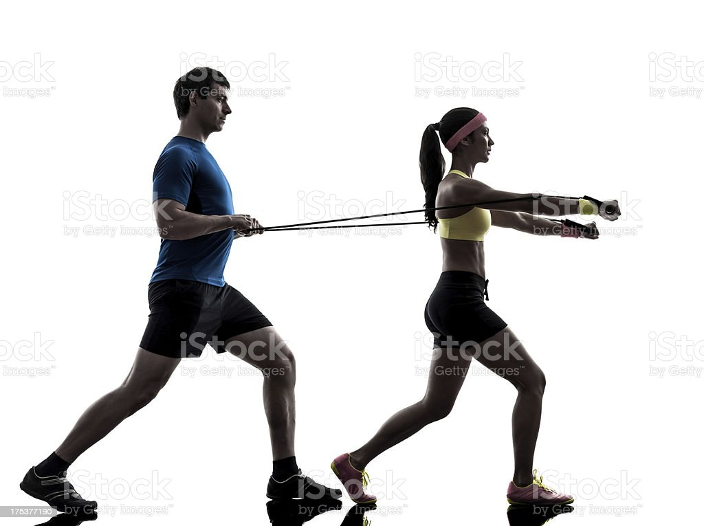 woman exercising fitness resistance  rubber band with man coach royalty-free stock photo