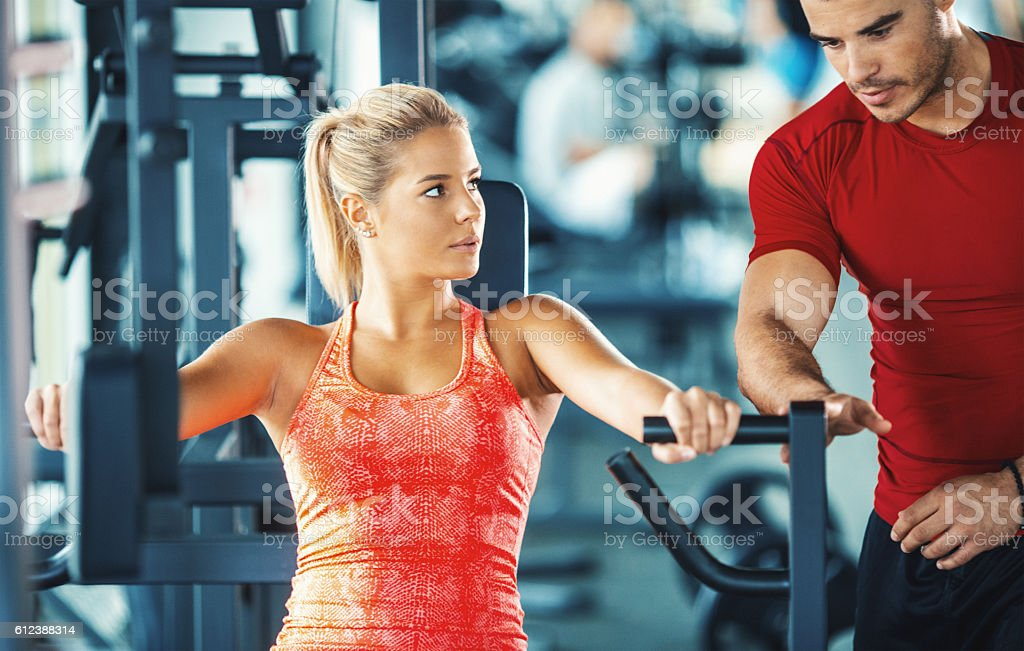 Woman exercising in a gym with an instructor. stock photo
