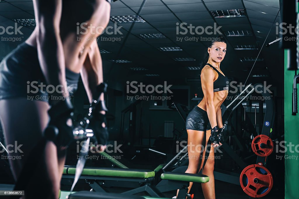Woman exercising in trainer for triceps muscles in the gym stock photo