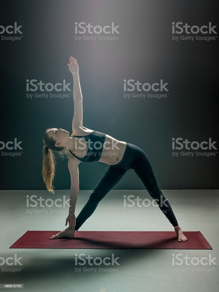 Woman exercising in triangle position stock photo