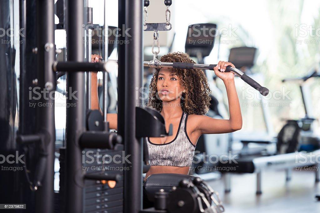 Woman exercising lat pulldown. Back and lat workout. stock photo