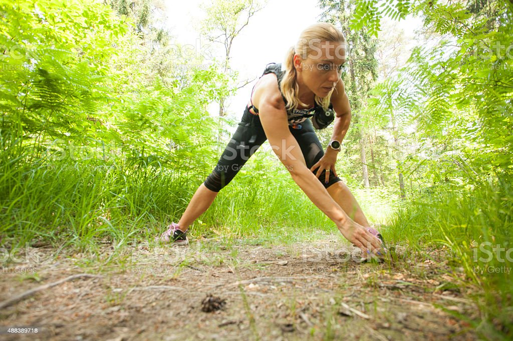 Woman exercising on forest trail stock photo