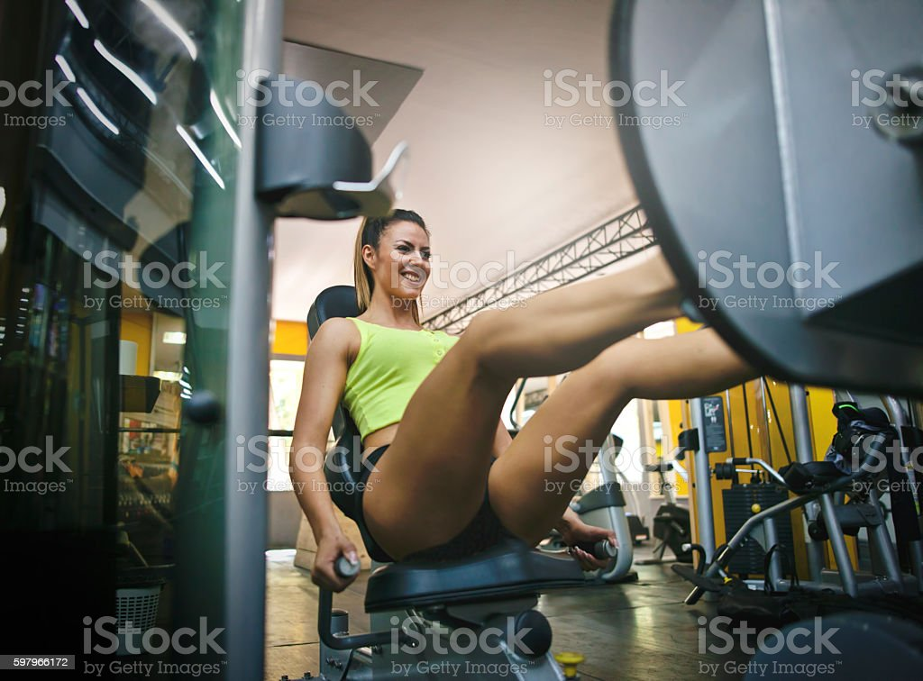 Woman exercising on leg press in gym stock photo