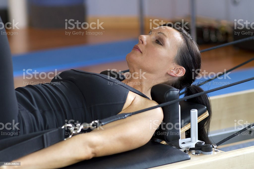 Woman Exercising on Pilates Reformer stock photo