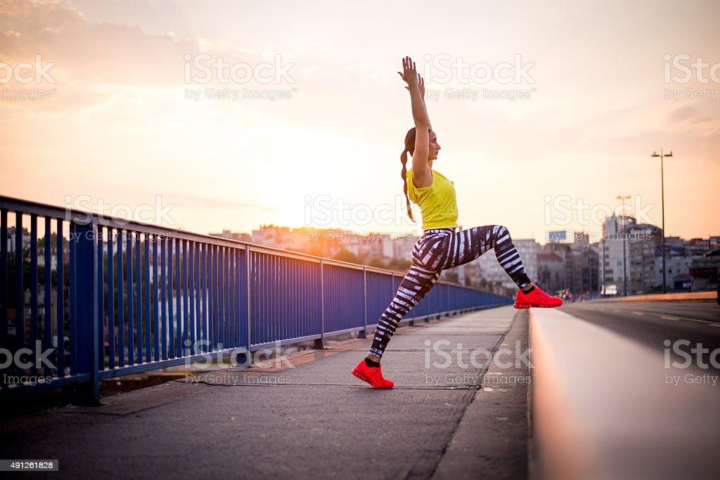 Woman exercising on the bridge stock photo