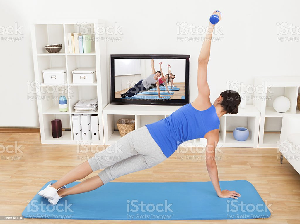 Woman exercising on yoga mat in front of TV stock photo