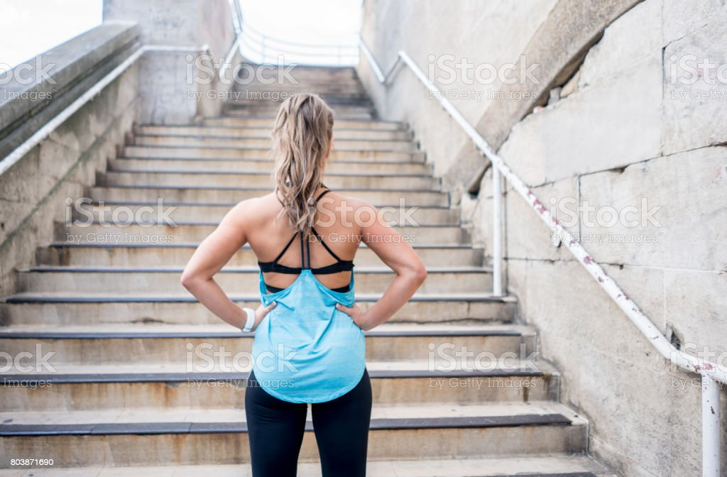 Woman exercising outdoors and looking at some stairs stock photo